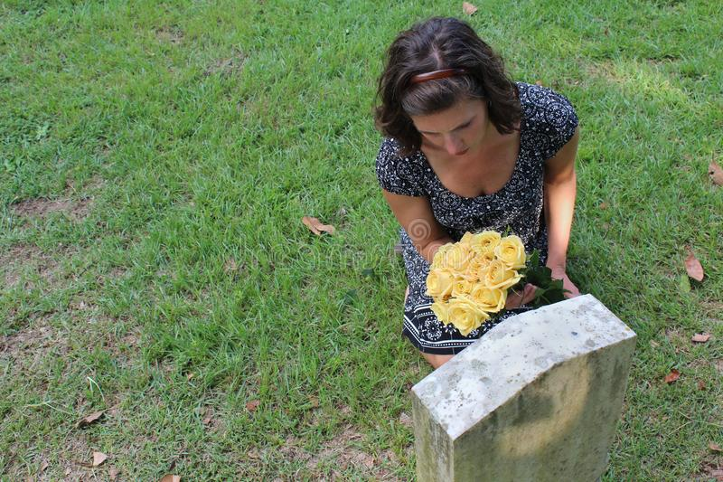 Woman at grave stone with yellow flowers. royalty free stock photo