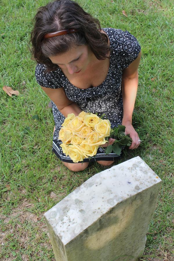 Woman at grave stone with yellow flowers. stock photos