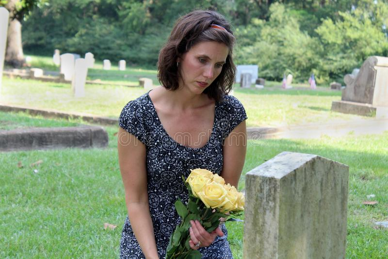 Woman at grave stone with yellow flowers. stock photo