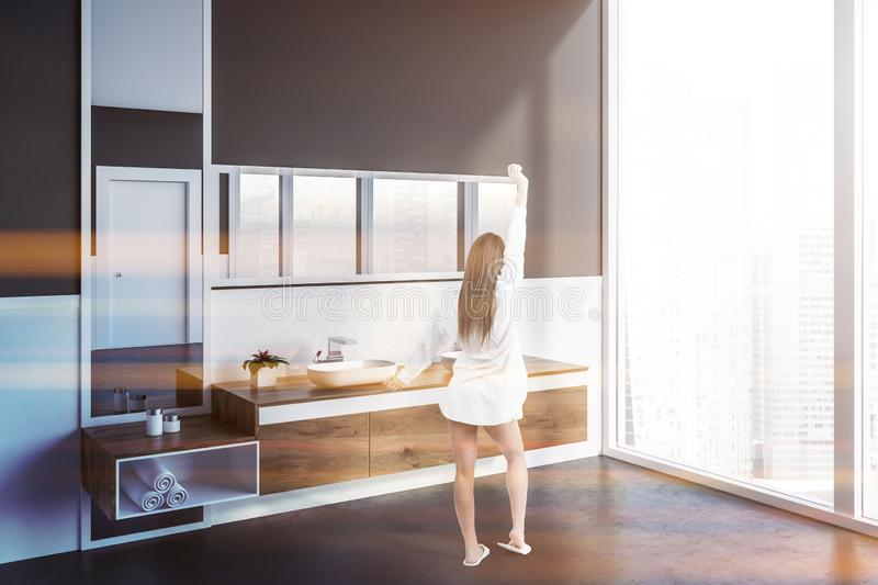 Woman in gray bathroom with double sink. Woman in corner of modern bathroom with white and gray walls, concrete floor, double sink standing on wooden countertop stock photos