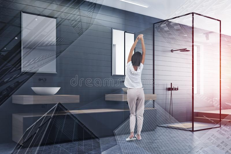 Woman in gray bathroom with shower and sink royalty free stock photos