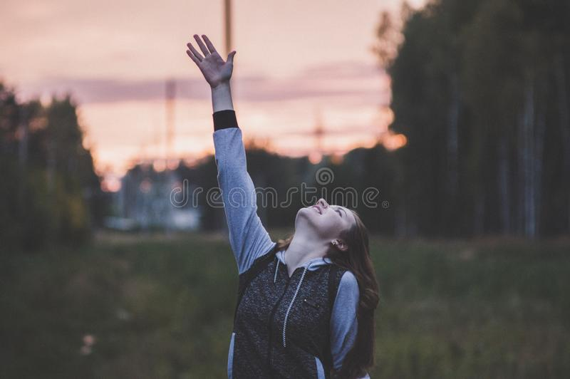 Woman in Gray and Black Zip-up Hoodie Raising Her Right Hand royalty free stock photos