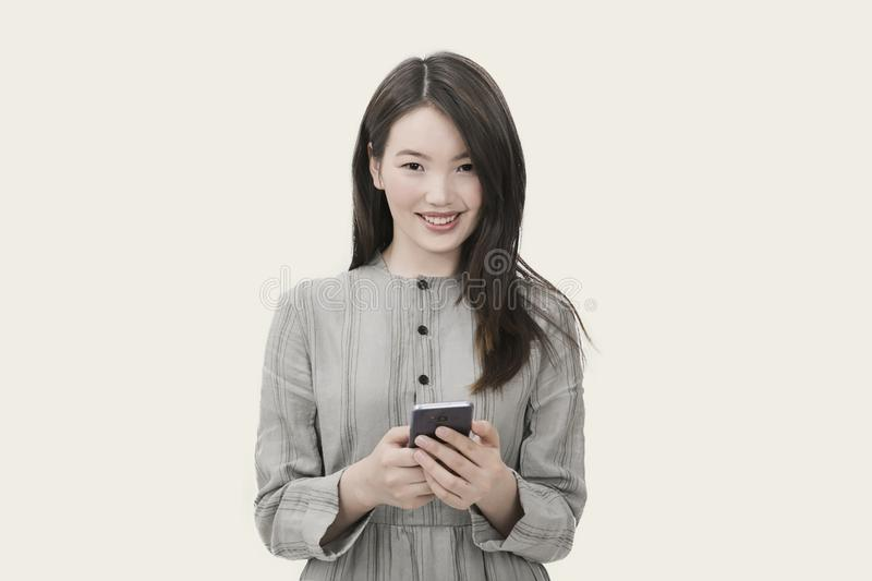 Woman in Gray Button-up Long-sleeved Dress Holding Black Smartphone stock photography