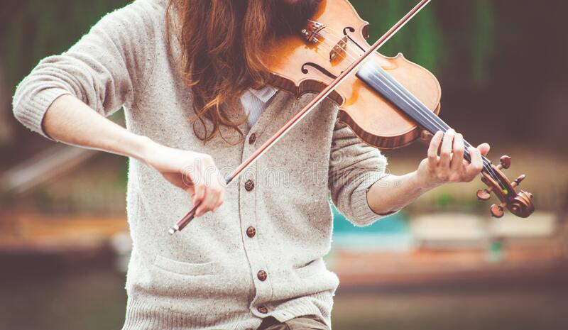 Woman in Gray Cardigan Playing a Violin during Daytime stock images
