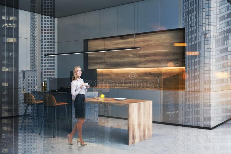 Woman in gray kitchen with bar stock photo