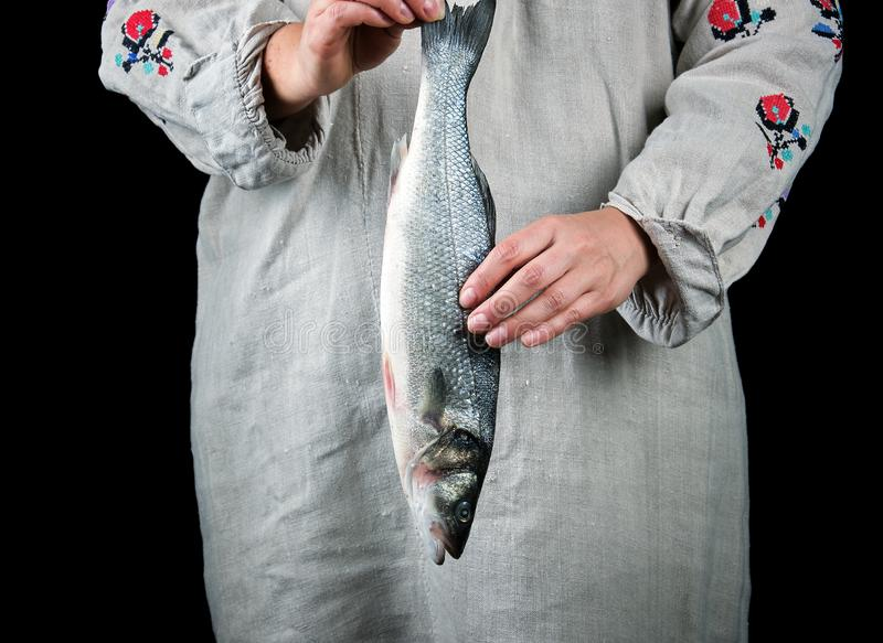 woman in gray linen clothes holding a fresh sea bass fish stock photo
