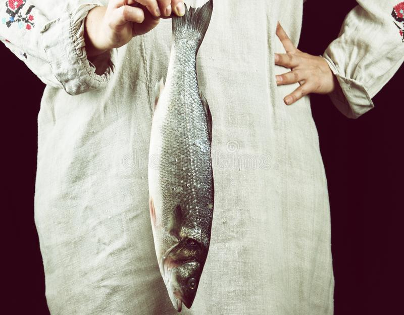 woman in gray linen clothes holding a fresh sea bass fish royalty free stock image