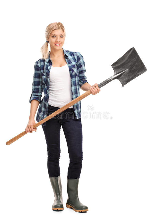 Woman in gray rubber boots holding a shovel stock images