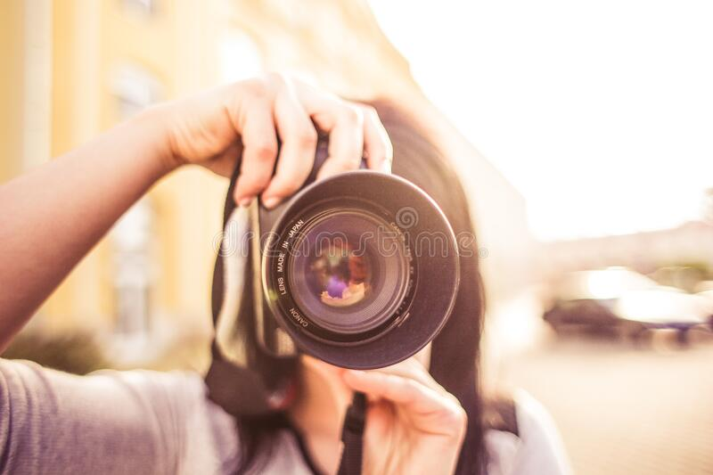 Woman in Gray Shirt Taking a Photo Shoot during Day Time stock photo