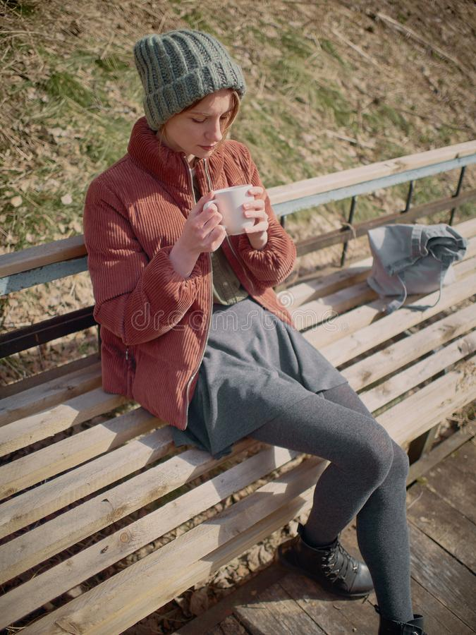 A woman in a gray skirt and pantyhose, wearing a green hat and a red jacket, sits on bench and drinks tea. stock photo