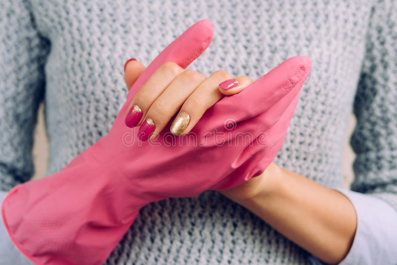 Woman in a gray sweater and bright manicure wearing pink rubber. Gloves to clean the house stock photo