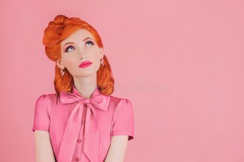 Woman with great idea in pink retro dress. Minimal color concept. Redhead model with retro hairstyle on pastel pink background. stock images