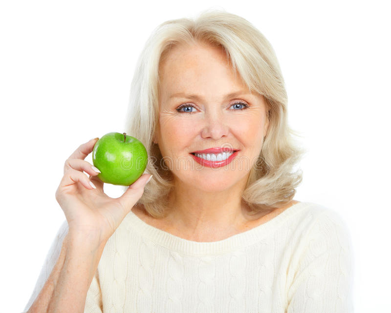 Woman with a green apple. Mature smiling woman with a green apple stock photo