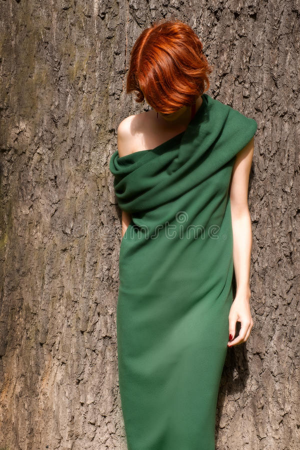 Woman in green dress against giant oak tree. Red-headed woman in green dress against giant oak tree. Outdoor photo at bright sunny day stock photos