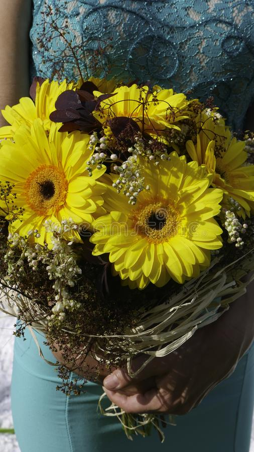 A woman in a green dress holds a bouquet of yellow Gerber - close up stock photography