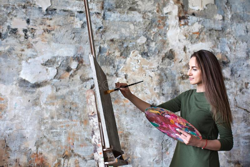 Woman in a green dress painting in an art studio royalty free stock images