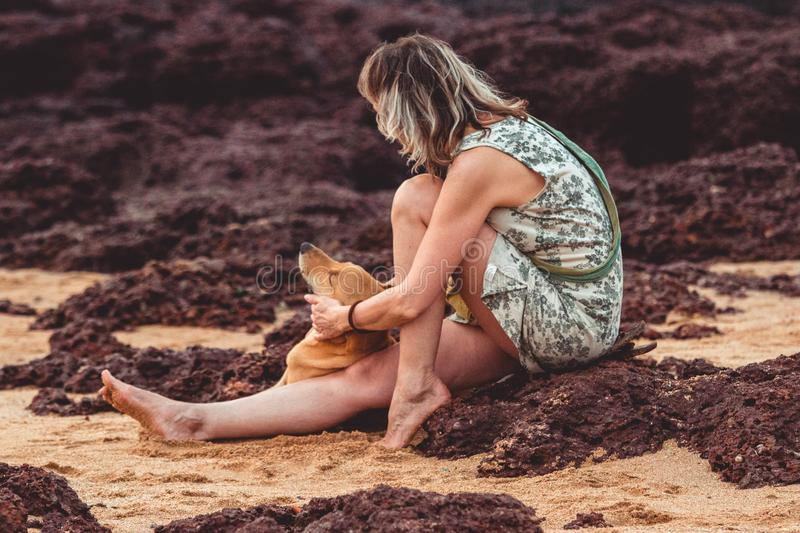 Woman With Green Floral Sleeveless Mini Dress Sitting on Brown Sand Close-up Photography stock photos