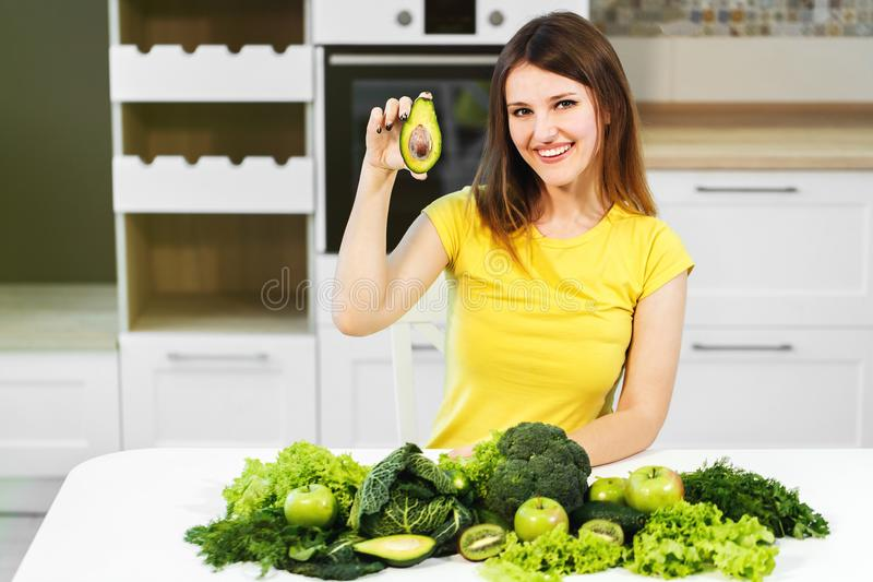 Woman with Green Food. Attractive caucasian woman, in yellow t-shirt sitting at big white table full of healthy green food stock image