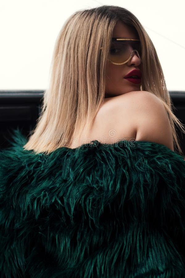 Woman in Green Fur Jacket Wearing Sunglasses With Gold Frame stock image