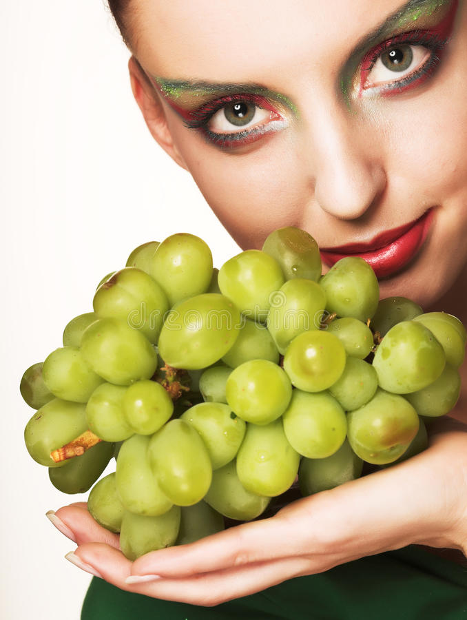 Woman with green grapes. Portrait of young attractive woman with green grapes royalty free stock image
