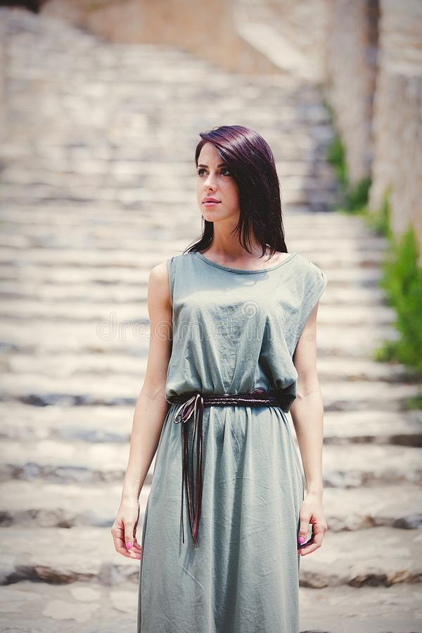 Woman in green gress waking down stairs on Greece street. Summer travel time image stock photography