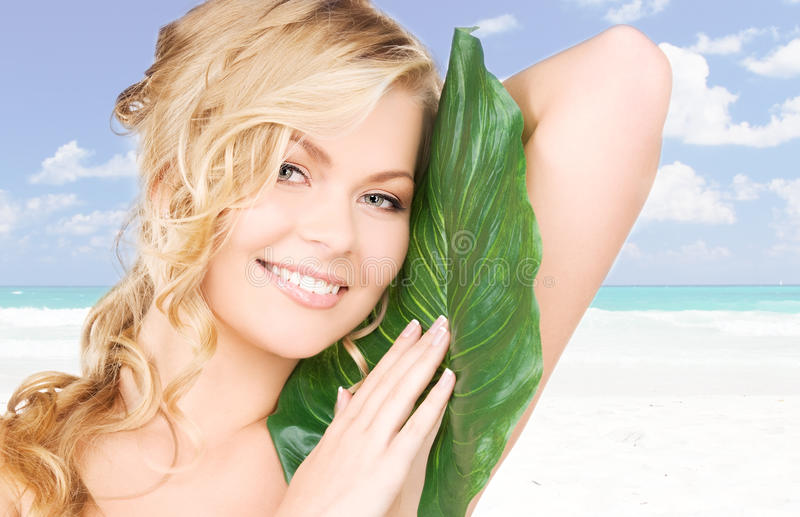 Download Woman With Green Leaf Over Beach Background Stock Photo - Image: 40668513