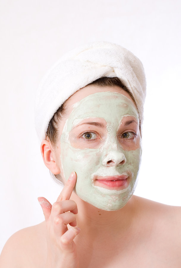 Woman with green mask on her face, cream stock image