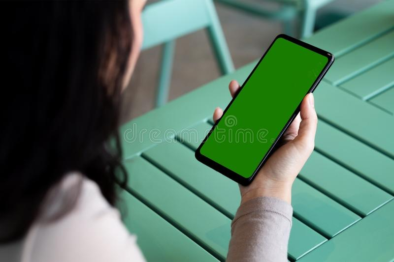 A woman and green screen on black smartphone royalty free stock images