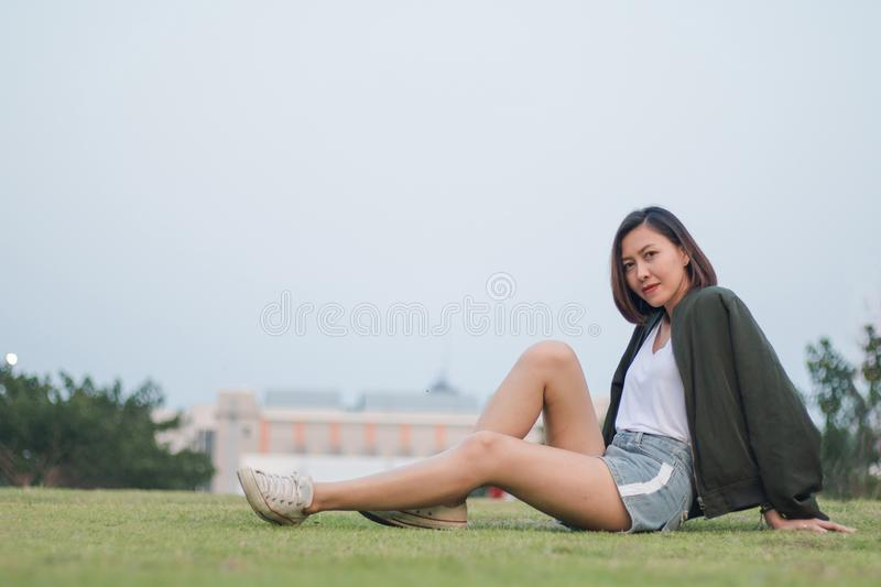 Woman green shirt sitting on the grass stock image