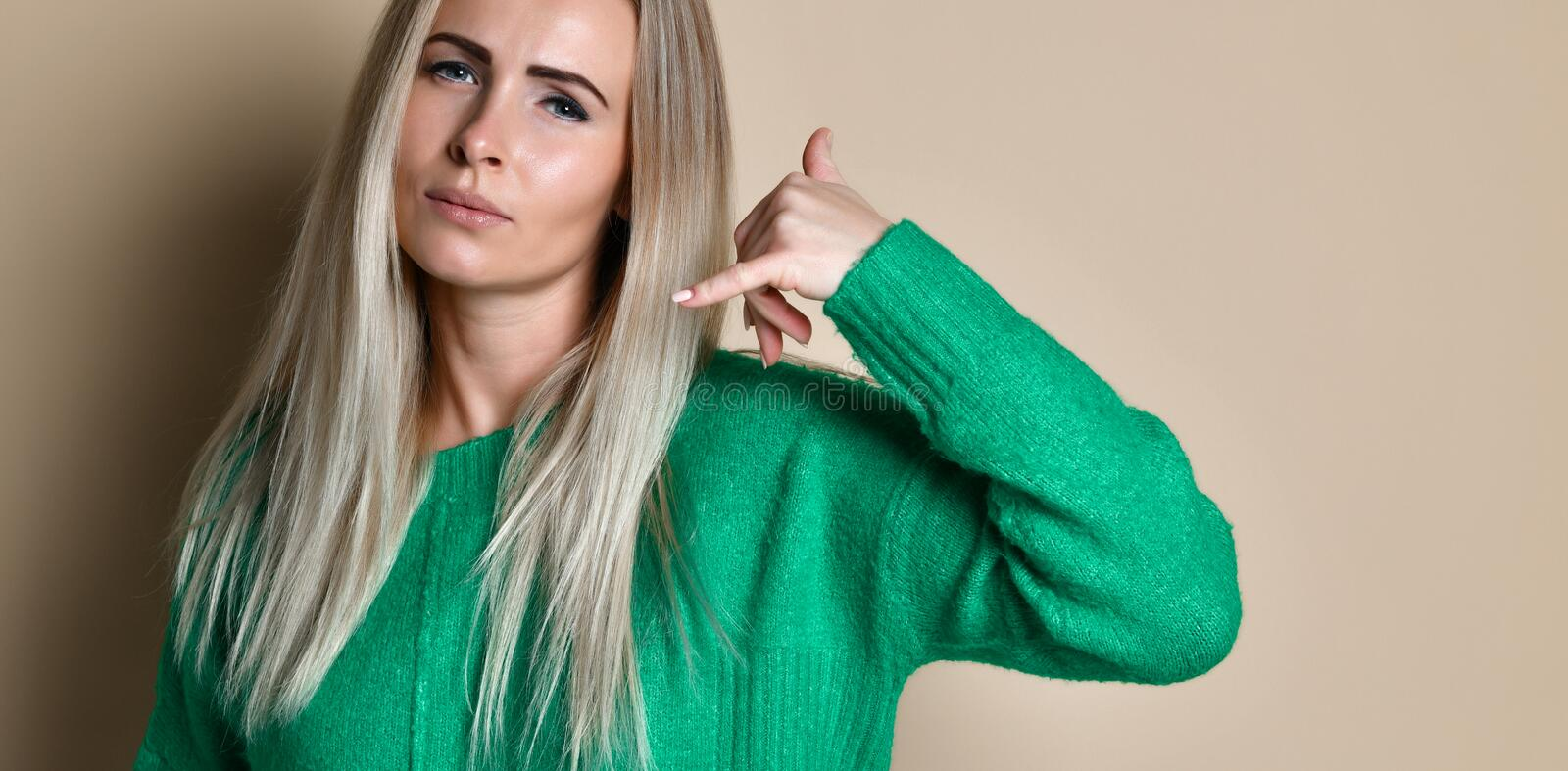 Woman in green sweater doing phone gesture like says: call me back with hand and fingers like talking on the telephone royalty free stock images