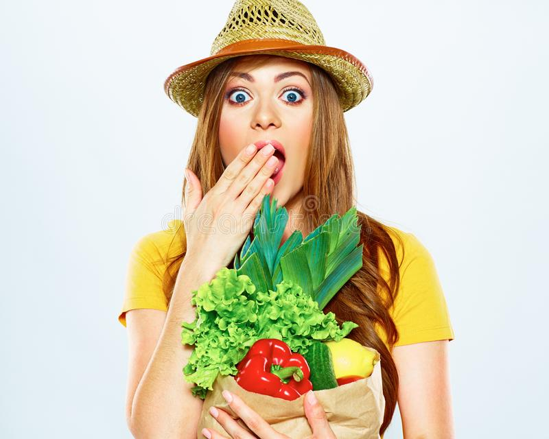 Woman with green vegan food. paper bag. surprise emotion. White background stock photo