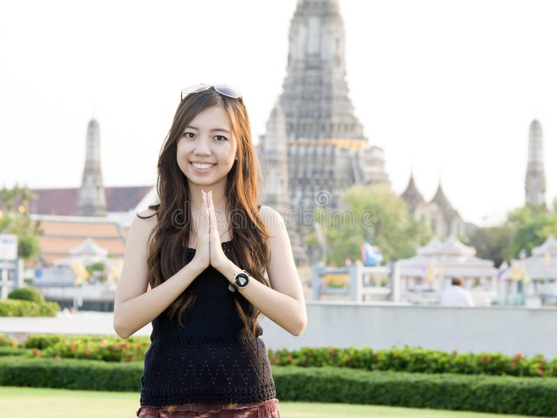 Woman greeting with Temple of Dawn royalty free stock image
