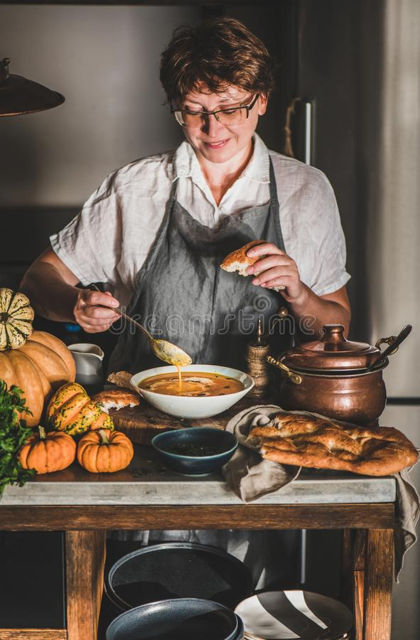 Woman in grey apron cooking and tasting pumpkin soup royalty free stock photo