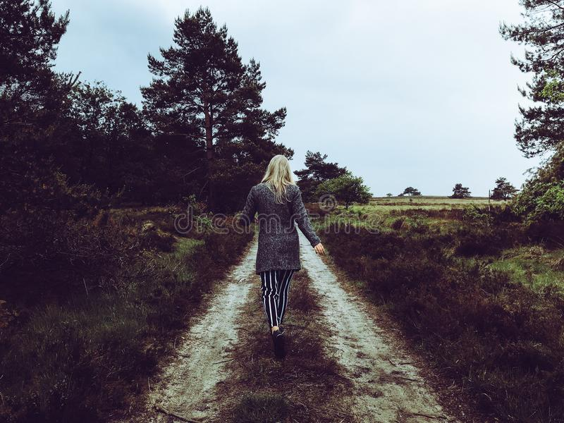 Woman in Grey Cardigan With Grey and Black Striped Pants Walking at the Pathway stock images