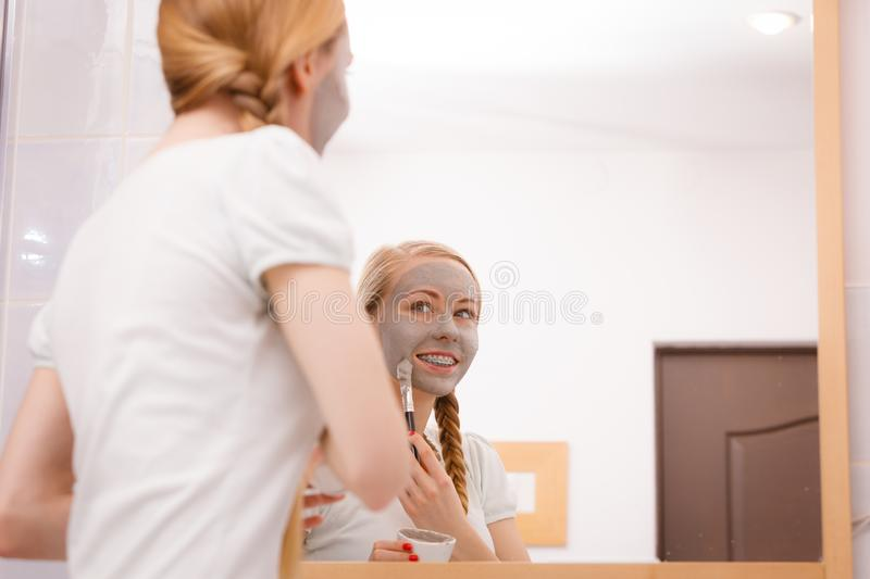 Woman with grey clay mud mask on her face. Skincare. Blonde woman in bathroom with gray clay mud mask on her face. Young lady taking care of skin. Spa beauty royalty free stock images