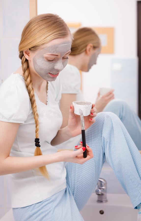 Woman with grey clay mud mask on her face. Skincare. Blonde woman in bathroom with gray clay mud mask on her face. Young lady taking care of skin. Spa beauty stock photography