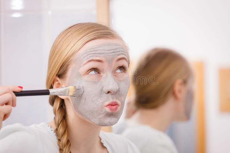 Woman with grey clay mud mask on her face. Skincare. Blonde woman in bathroom with gray clay mud mask on her face. Young lady taking care of skin. Spa beauty stock image