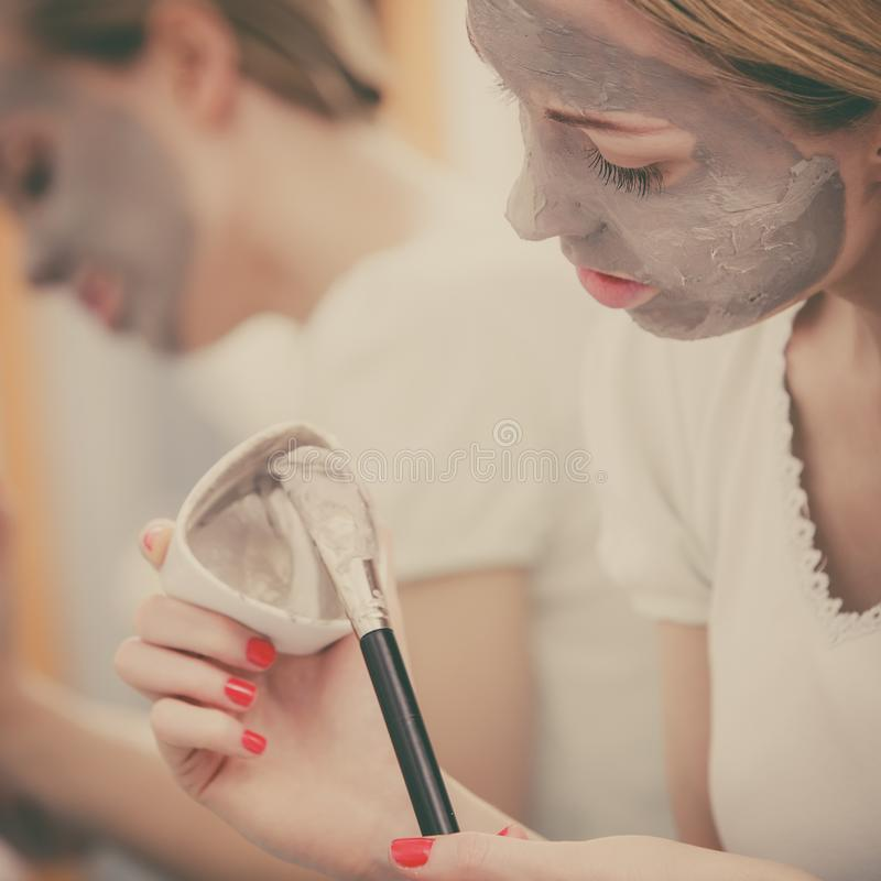 Woman with grey clay mud mask on her face. Skincare. Blonde woman in bathroom with gray clay mud mask on her face. Young lady taking care of skin. Spa beauty royalty free stock photos