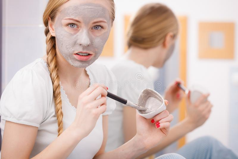 Woman with grey clay mud mask on her face. Skincare. Blonde woman in bathroom with gray clay mud mask on her face. Young lady taking care of skin. Spa beauty royalty free stock image