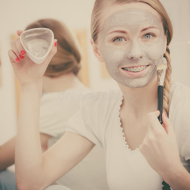 Woman with grey clay mud mask on her face. Skincare. Blonde woman in bathroom with gray clay mud mask on her face. Young lady taking care of skin. Spa beauty royalty free stock photo