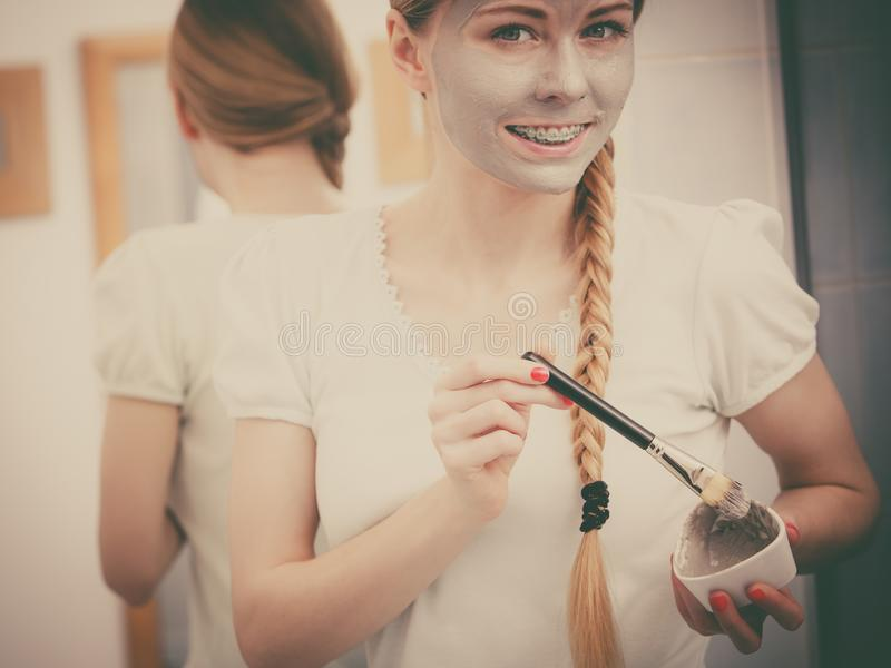 Woman with grey clay mud mask on her face. Skincare. Blonde woman in bathroom with gray clay mud mask on her face. Young lady taking care of skin. Spa beauty stock photo