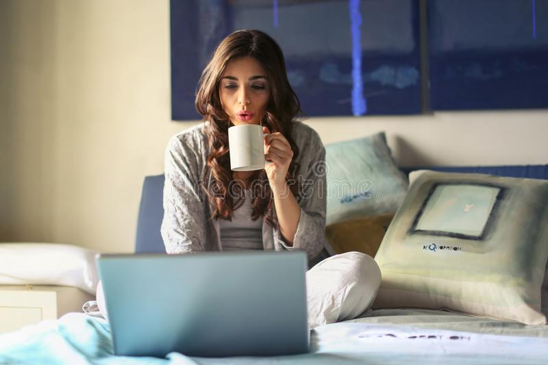 Woman in Grey Jacket Sits on Bed Uses Grey Laptop royalty free stock photo