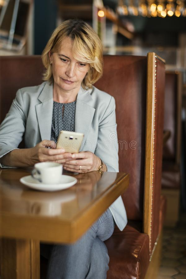 Woman in Grey Notched Lapel Suit Jacket Holding Smartphone Sitting Beside Wooden Table royalty free stock photos