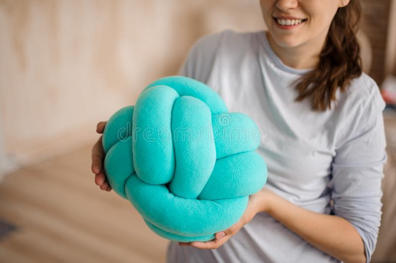 Smiling woman holding a cute blue knot pillow stock photos