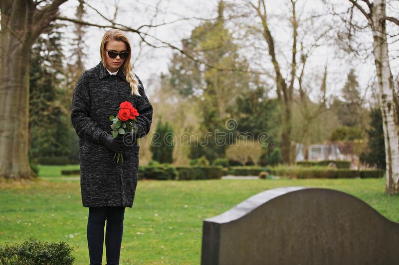 Woman grieving at cemetery holding flowers. Young woman standing at graveside of a deceased family member. Female at cemetery grieving holding flowers stock photos