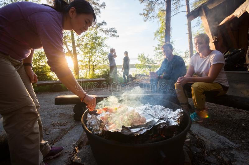 Woman Grilling Food On Skewers With Friends In Background royalty free stock images