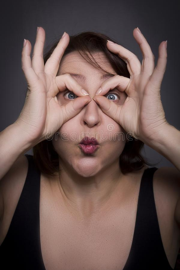 Woman grimaces in front of camera. On black background royalty free stock photography