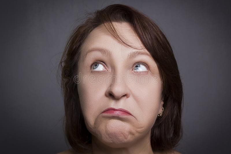 Woman grimaces in front of camera. On black background royalty free stock images