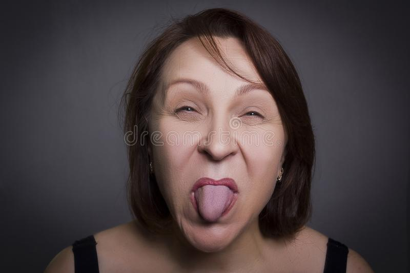 Woman grimaces in front of camera. On black background royalty free stock photos