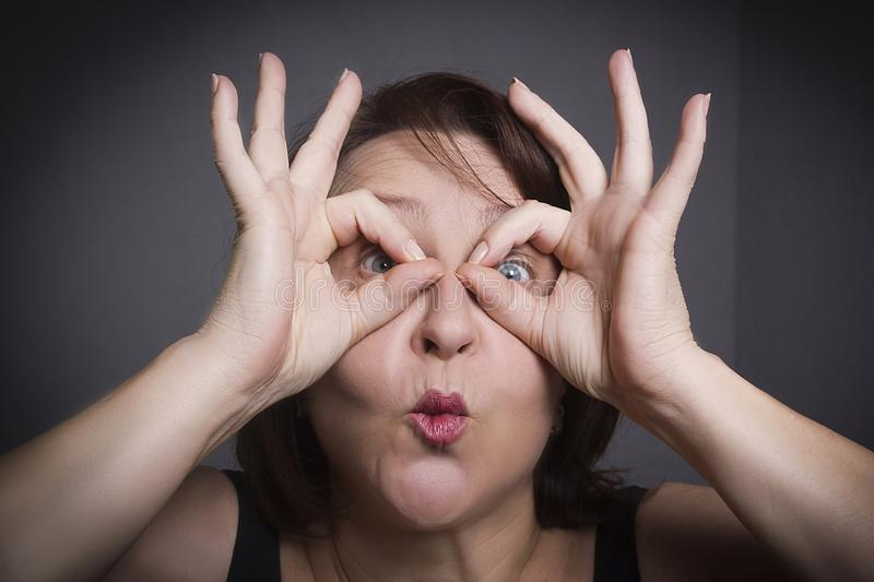 Woman grimaces in front of camera. On black background stock photo